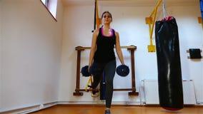 Mujer joven morena hermosa que hace ejercicios en el gimnasio almacen de video