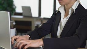 Mujer joven motivada en café de consumición del traje de negocios y trabajo en el ordenador portátil almacen de metraje de vídeo