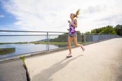 Mujer joven motivada que corre rápidamente en el puente sobre un lago Fotografía de archivo libre de regalías