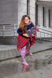 Mujer joven - muchacha con el pelo largo en vidrios, con una cesta de uvas, sonriendo feliz, en las botas de goma que se colocan  Fotografía de archivo libre de regalías
