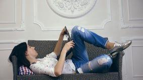 Mujer joven, muchacha, morenita, en la camisa blanca y los vaqueros, mintiendo en un sofá, pequeño sofá, con el ordenador portáti metrajes