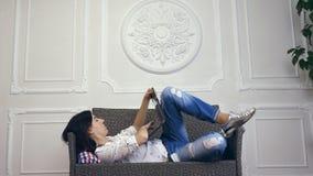 Mujer joven, muchacha, morenita, en la camisa blanca y los vaqueros, mintiendo en un sofá, pequeño sofá, con el ordenador portáti almacen de video