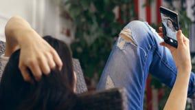 Mujer joven, muchacha, morenita, en la camisa blanca y los vaqueros, mintiendo en un sofá, pequeño sofá, con smartphone El escuch almacen de metraje de vídeo
