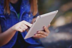 Mujer joven, muchacha que trabaja con la tableta en el campo verde, parque imagenes de archivo