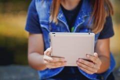 Mujer joven, muchacha que trabaja con la tableta en el campo verde, parque Fotos de archivo