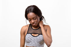Mujer joven muscular cansada que frota su cuello Foto de archivo