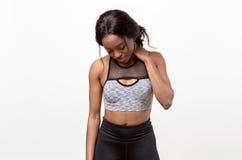 Mujer joven muscular cansada que frota su cuello Fotos de archivo libres de regalías