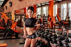 Mujer joven muscular con el cuerpo hermoso que hace ejercicios con pesa de gimnasia fotos de archivo