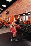 Mujer joven muscular con el cuerpo hermoso que hace ejercicios con pesa de gimnasia fotos de archivo libres de regalías
