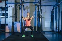 Mujer joven muscular de la aptitud que levanta un crossfit del peso en el gimnasio Barbell del deadlift de la mujer de la aptitud foto de archivo libre de regalías