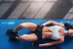 Mujer joven muscular que miente en la estera del ejercicio Fotografía de archivo libre de regalías