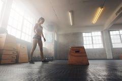 Mujer joven muscular que se resuelve con una caja en el gimnasio del crossfit fotografía de archivo