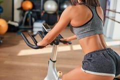 Mujer joven muscular que se resuelve en la bicicleta estática en el gimnasio Imágenes de archivo libres de regalías
