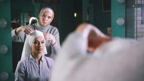 Mujer joven musulmán que prepara el tocado islámico de la boda para la novia joven delante del espejo Imagen de archivo libre de regalías