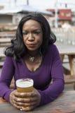 La mujer joven enojada del afroamericano bebe la pinta de cerveza clara Fotos de archivo libres de regalías