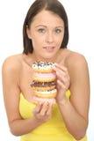 Mujer joven natural atractiva que sostiene una pila de anillos de espuma helados Fotos de archivo libres de regalías