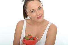 Mujer joven natural feliz sana que sostiene un cuenco de fresas jugosas maduras frescas Imágenes de archivo libres de regalías