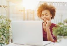 Mujer joven negra del freelancer con el ordenador portátil en el café al aire libre Fotografía de archivo libre de regalías