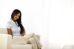 Mujer joven negra que hojea en la computadora portátil Fotografía de archivo libre de regalías