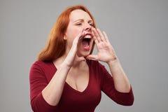 Mujer joven nerviosa con el grito rojo del pelo Foto de archivo libre de regalías