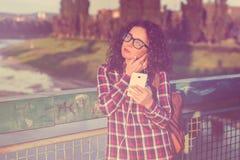 Mujer joven o adolescente con smartphone y auriculares sonrientes que escucha la música al aire libre entonado Fotografía de archivo