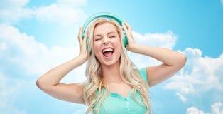 Mujer joven o adolescente feliz con los auriculares Imagen de archivo libre de regalías