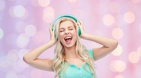 Mujer joven o adolescente feliz con los auriculares Fotografía de archivo libre de regalías