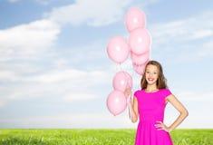 Mujer joven o adolescente feliz con los balones de aire del helio Imágenes de archivo libres de regalías