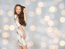 Mujer joven o adolescente feliz en vestido sobre luces Foto de archivo