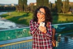 Mujer joven o adolescente sonriente con smartphone y el headphon Foto de archivo libre de regalías
