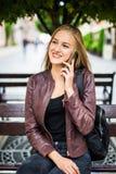 Mujer joven o adolescente sonriente que invita a smartphone en la calle de la ciudad Fotografía de archivo libre de regalías