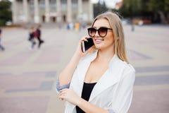 Mujer joven o adolescente sonriente que invita a smartphone en la calle de la ciudad Imagenes de archivo