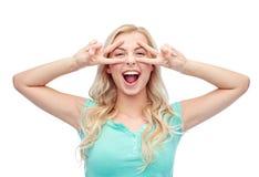 Mujer joven o adolescente sonriente que muestra paz Imagenes de archivo