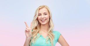 Mujer joven o adolescente sonriente que muestra paz Foto de archivo libre de regalías