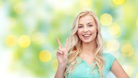 Mujer joven o adolescente sonriente que muestra paz Imágenes de archivo libres de regalías
