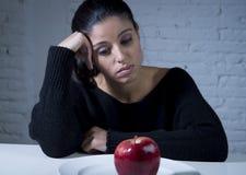 Mujer joven o fruta de mirada adolescente de la manzana en plato como símbolo de la dieta loca en trastorno alimenticio Fotografía de archivo libre de regalías