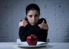 Mujer joven o fruta de mirada adolescente de la manzana en plato como símbolo de la dieta loca en trastorno alimenticio Fotografía de archivo