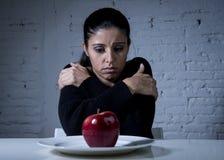 Mujer joven o fruta de mirada adolescente de la manzana en plato como símbolo de la dieta loca en trastorno alimenticio Imágenes de archivo libres de regalías