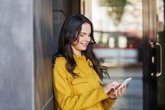 Mujer joven o muchacha sonriente que manda un SMS en smartphone Fotos de archivo libres de regalías