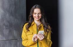 Mujer joven o muchacha sonriente que manda un SMS en smartphone Fotografía de archivo libre de regalías