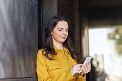 Mujer joven o muchacha sonriente que manda un SMS en smartphone Fotografía de archivo
