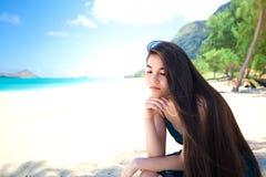 Mujer joven o sentada adolescente en la playa hawaiana, pensando Fotografía de archivo