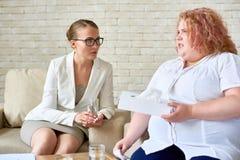 Mujer joven obesa que discute problemas mentales con Psychi femenino Imagen de archivo