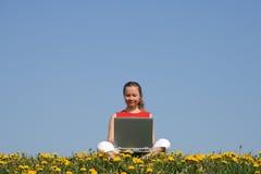 Mujer joven ocasional con la computadora portátil Imagen de archivo libre de regalías