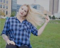 Mujer joven ocasional vestida en un parque de la ciudad Imágenes de archivo libres de regalías