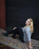 Mujer joven ocasional vestida que se sienta delante de la pared negra Fotografía de archivo