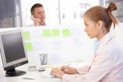 Mujer joven ocupada en oficina usando el ordenador Fotos de archivo