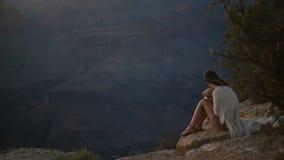 Mujer joven pacífica de la cámara lenta con el pelo del vuelo que se sienta en el panorama épico de la montaña de la puesta del s metrajes