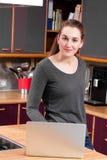 Mujer joven pacífica en la cocina que trabaja en el ordenador para el comercio electrónico Foto de archivo libre de regalías