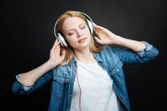 Mujer joven pacífica que escucha la música dentro Fotografía de archivo